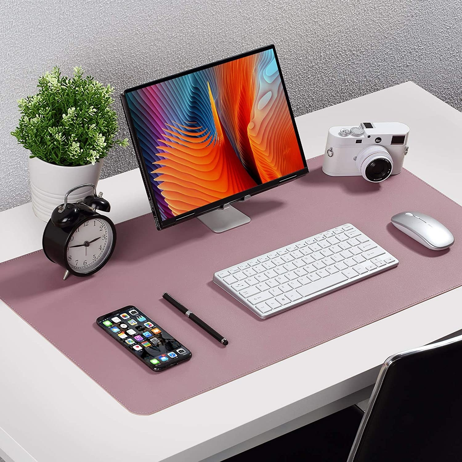 A desk pad with a computer, phone, camera, and various other desk accessories on it