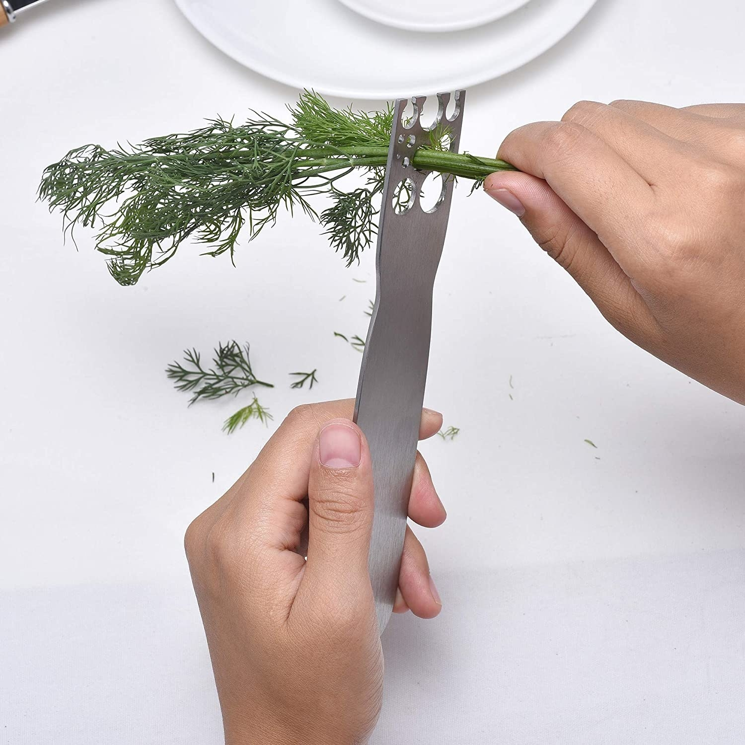 A person using the tool to strip dill off its stem