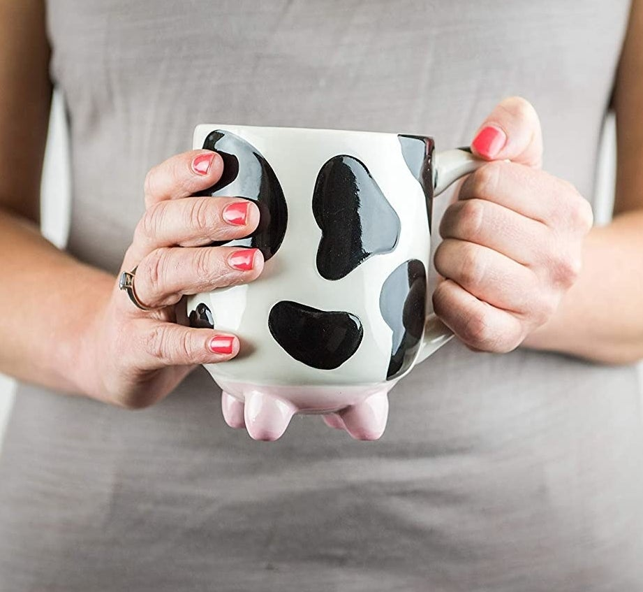 A person holding the cow-shaped mug