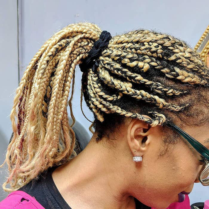 A person using the hair tie to hold their braids in a ponytail