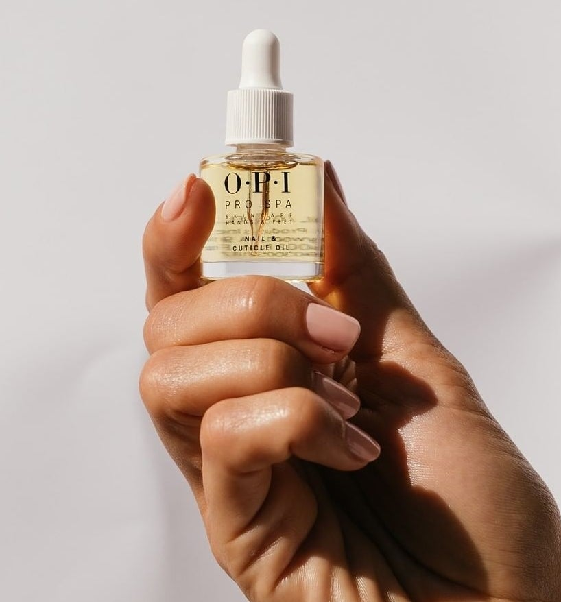A person holding a bottle of cuticle oil