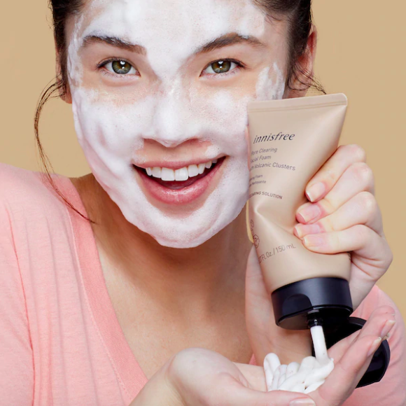 model with foaming face wash and squeezing a bottle of product into hand