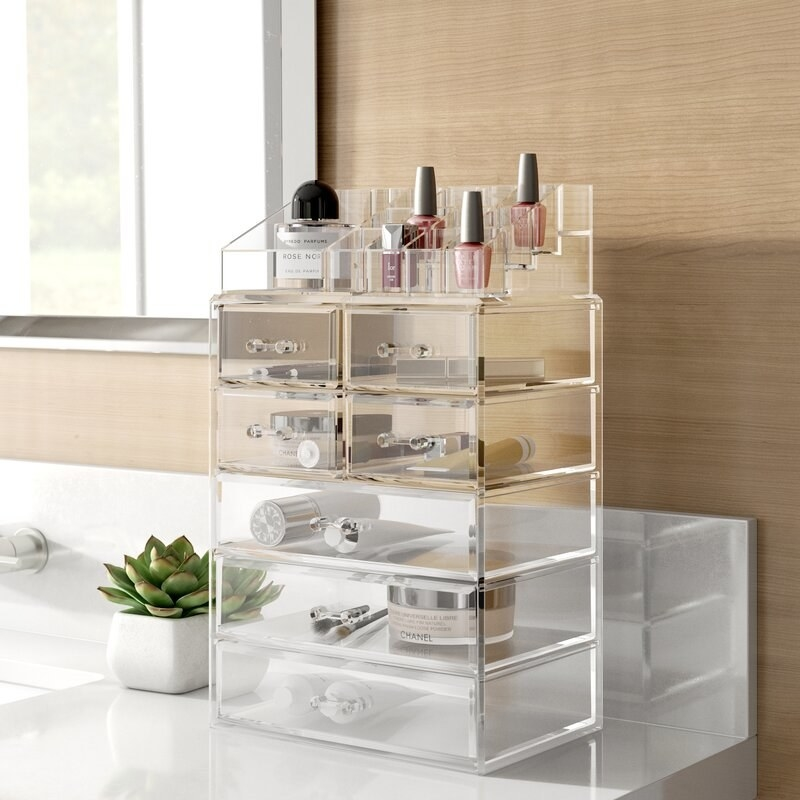 A bathroom counter with a clear acrylic container