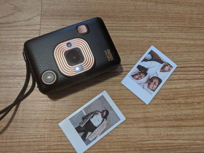 A small camera with two instant photographs beside it