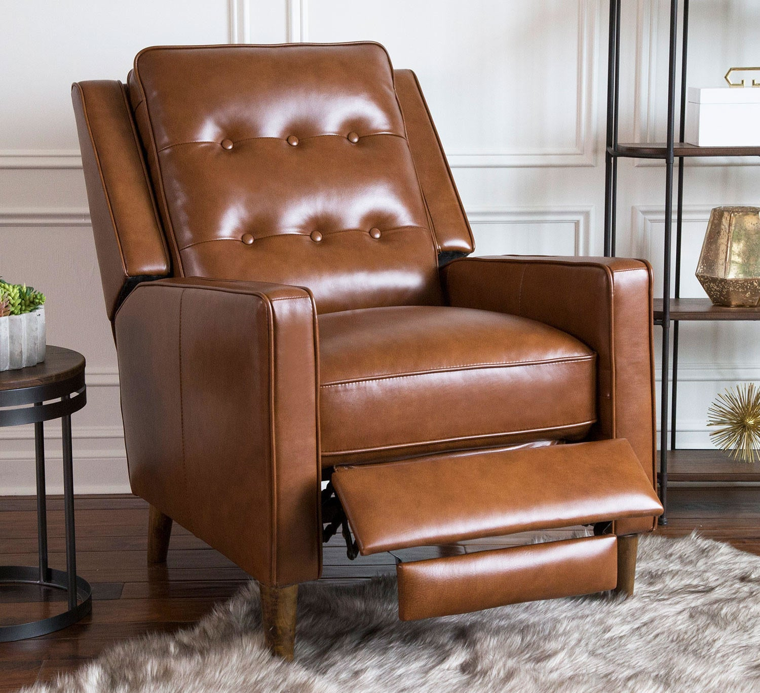 The brown leather recliner, which has a footrest