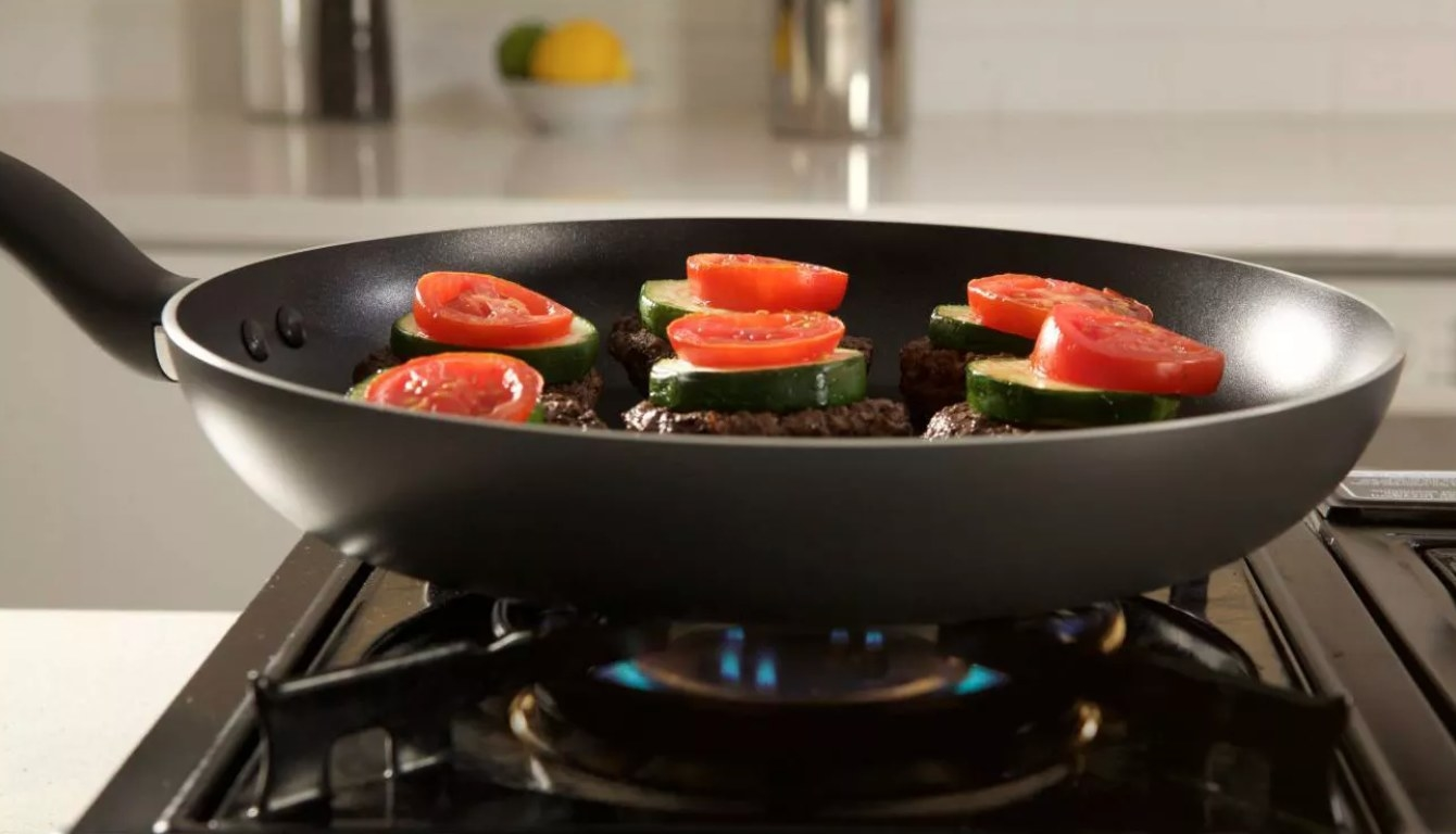 The saute pan in black being used to cook veggies on a burner