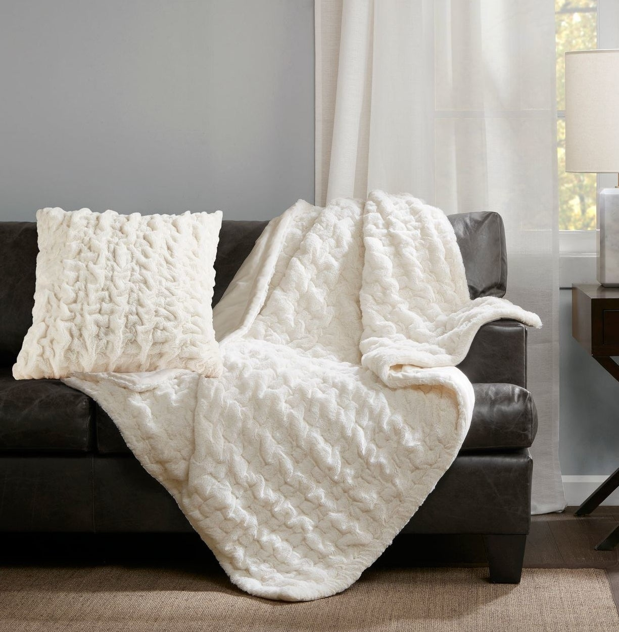 The throw in white draped over a couch beside a matching pillow
