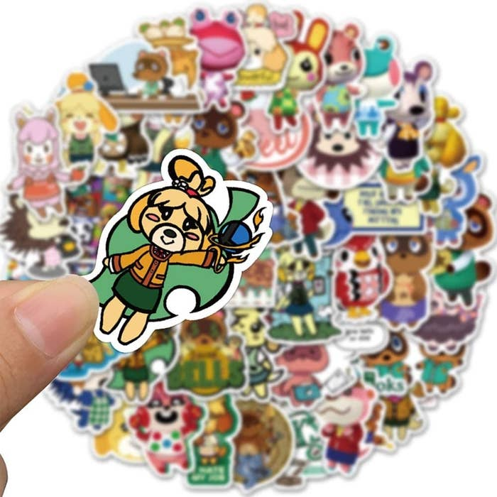 A person holding a sticker in their hand above a pile of other stickers