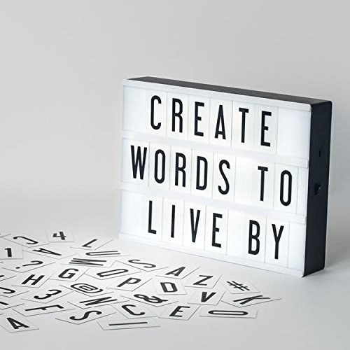 """A lightbox that says """"Create words to live by"""" and an assortment of letters and symbols strewn near it"""