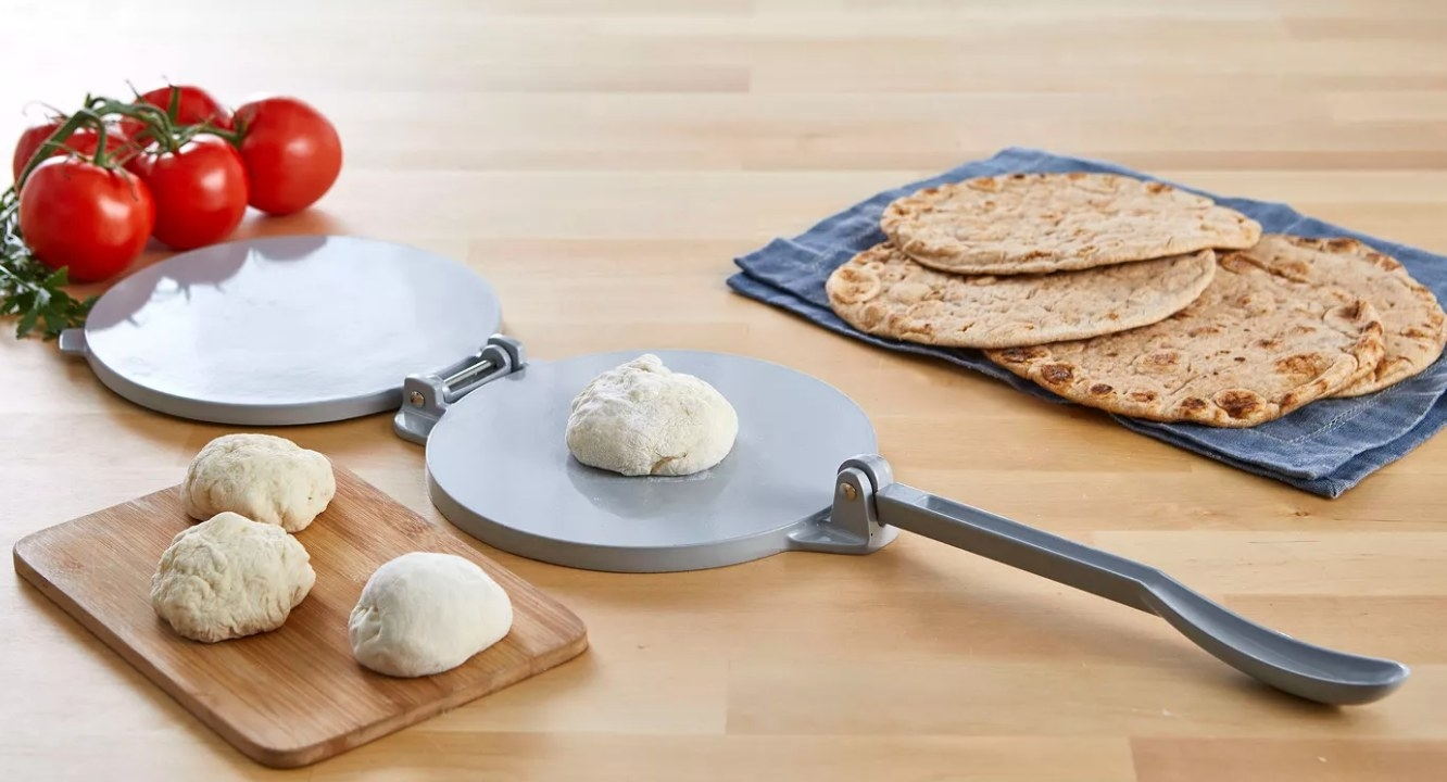 The tortilla press in silver with a handle for leverage