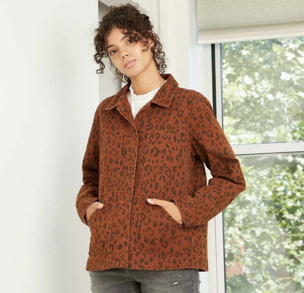 Model wearing rust colored jacket with black cheetah print