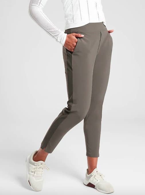 Model wears olive green Brooklyn Ankle Pant with a white sweater and white and brown sneakers