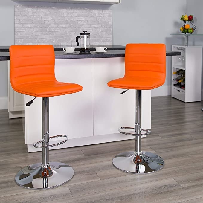 Two orange armless chairs with a long leg and a circular base