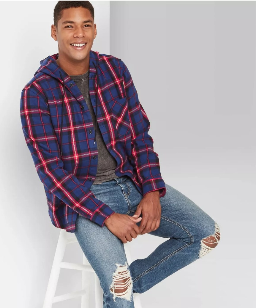 Model wearing blue and red flannel hoodie with ripped jeans and gray undershirt