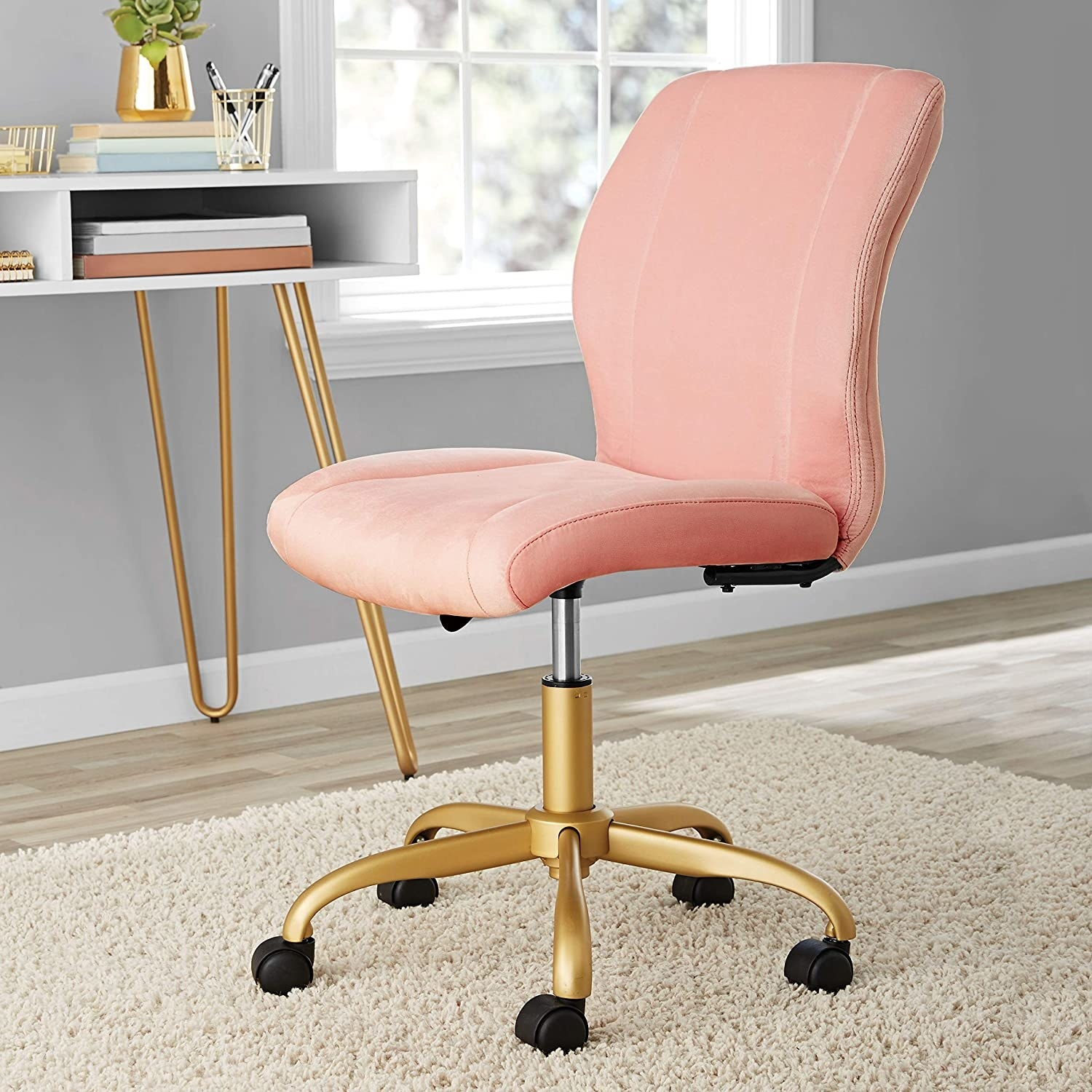 A pink armless desk chair with gold-toned rolling legs