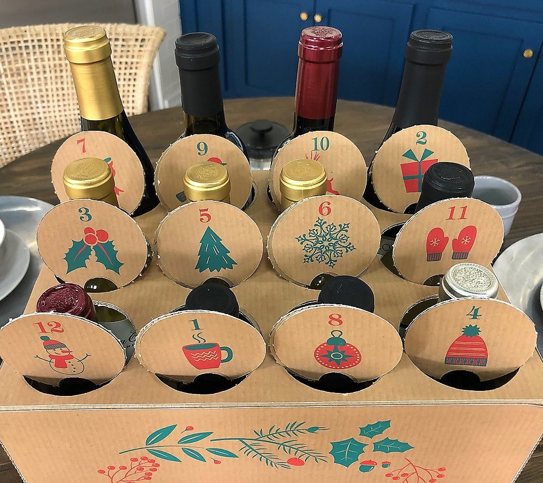 a cardboard carton with holes punched in the top for 12 days with a wine bottle in each one