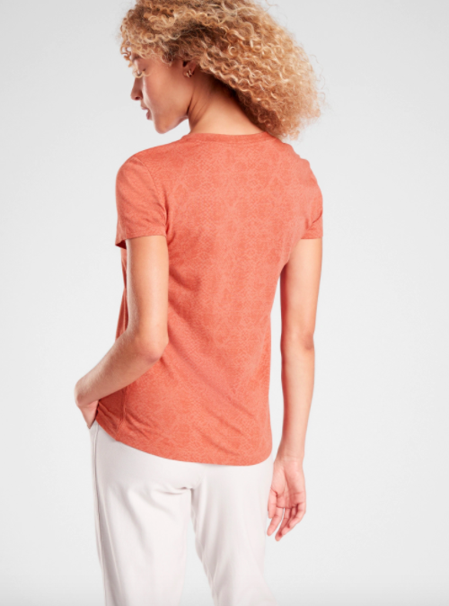 Model wears light red snakeskin-print workout tee with white pants