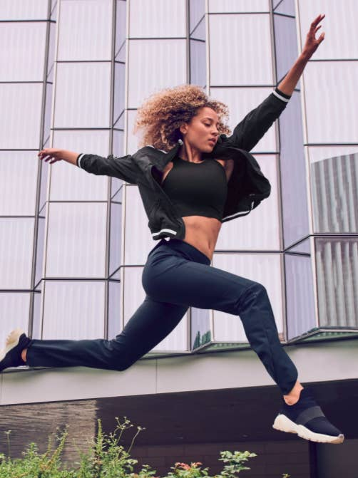 Model wears black Athleta Conscious Crop with black joggers, a hoodie, and sneakers