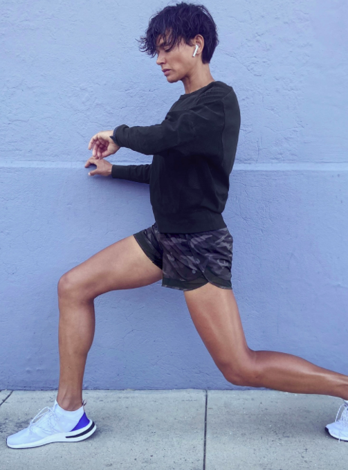 Model wears black and gray camo-print running shorts with a black sweatshirt and white sneakers