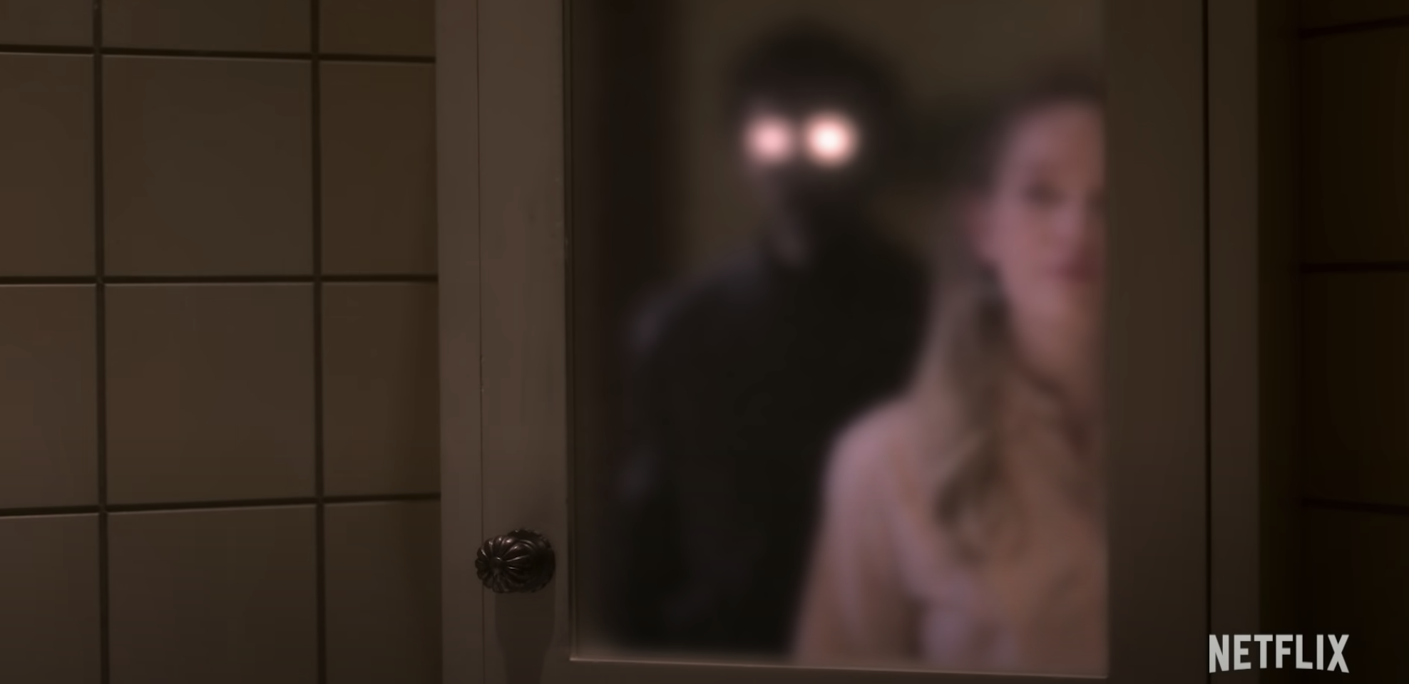 Dani looking in the mirror and seeing a ghost behind her
