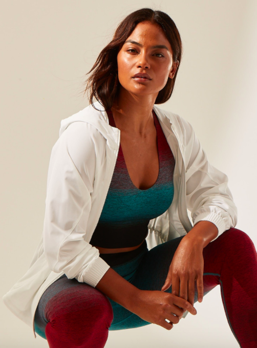 Model wears white running jacket with a green and red ombre crop top and running leggings