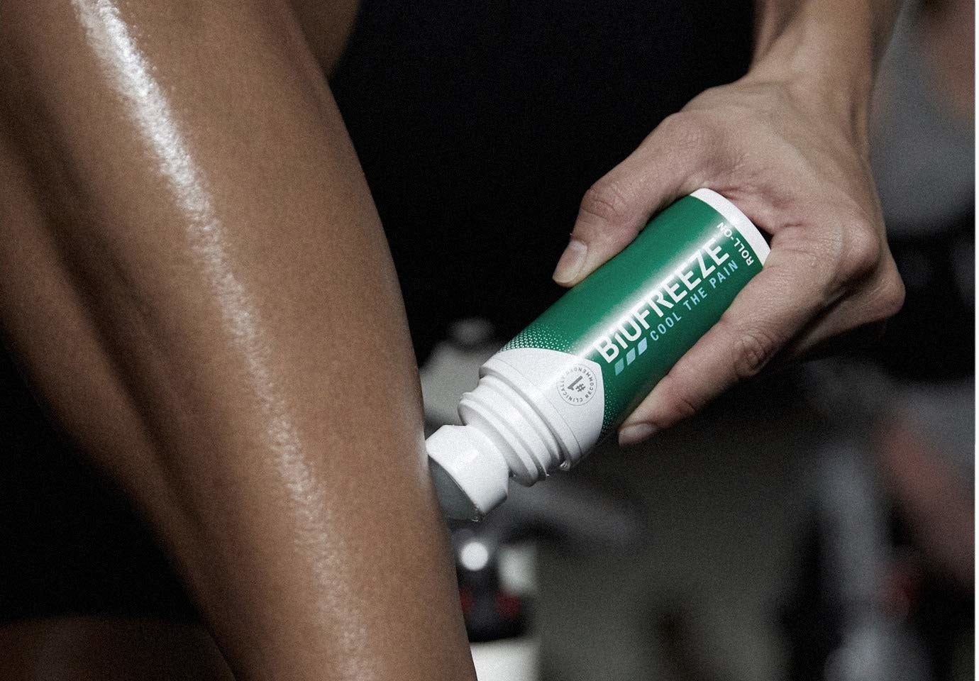 Person applying Biofreeze roll-on gel to side of leg