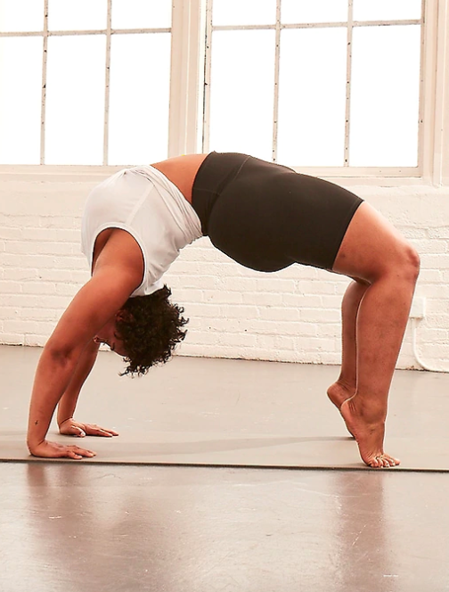 Model wears high-rise black bike shorts with a white crop twist -front tank while practicing bridge pose on a mat