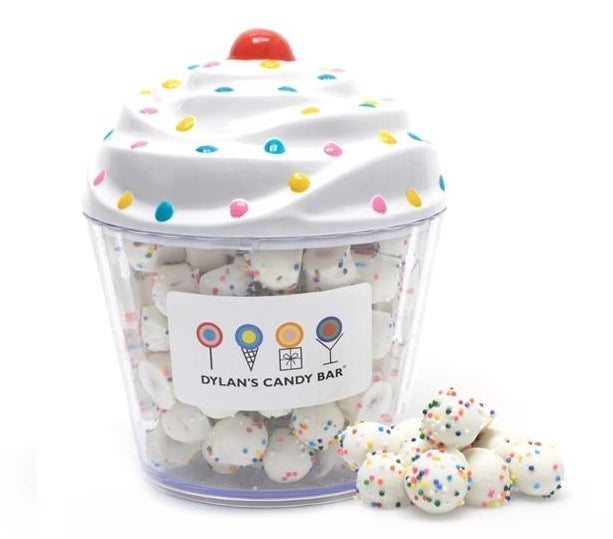 A plastic cupcake container with the balls covered in rainbow nonpareils inside