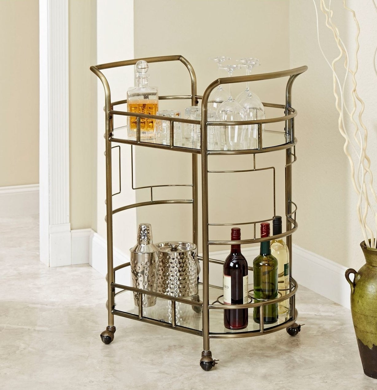 The 2 tiered bar cart with glasses on the first tier and wine in the 3 wine holders on the second tier