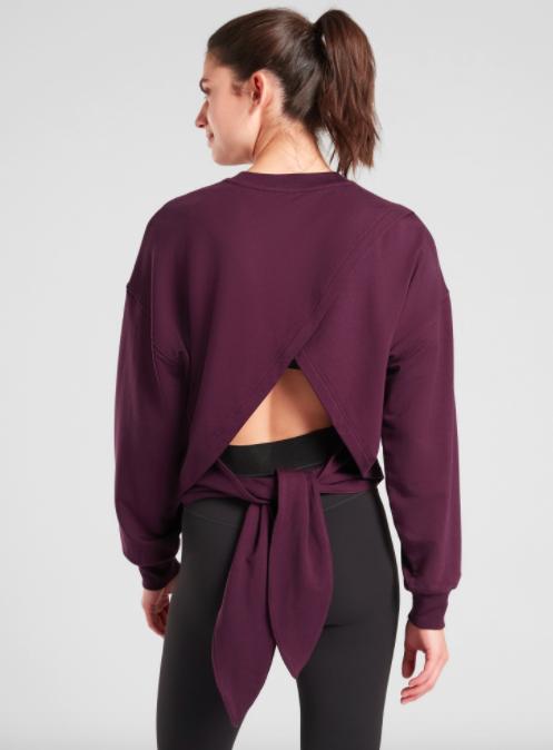 Model wears plum-colored tie back sweatshirt with black yoga leggings
