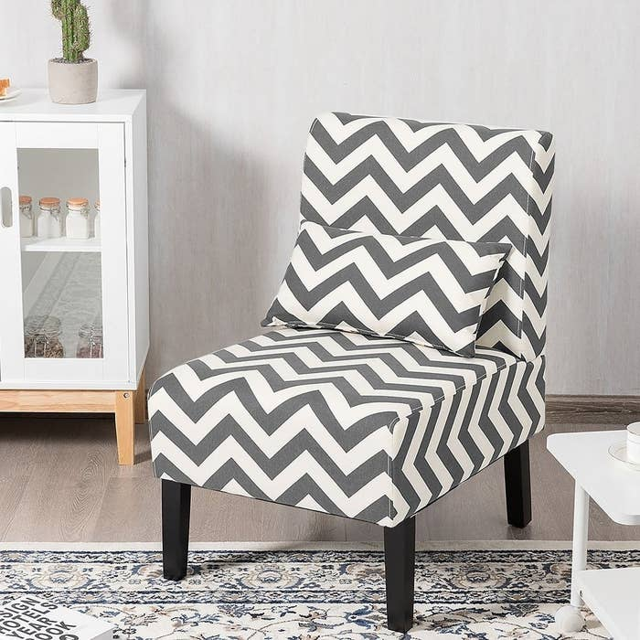 The gray and white armless chair with a matching lumbar pillow and black legs