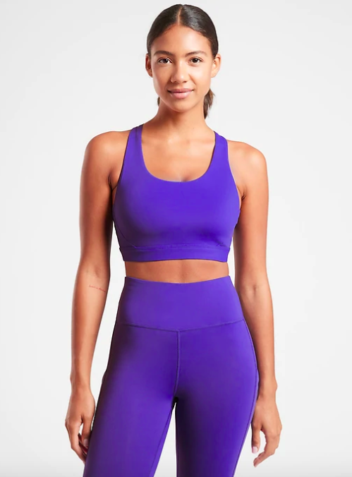 Model wears a blue-violet scoop neck sports bra with matching leggings