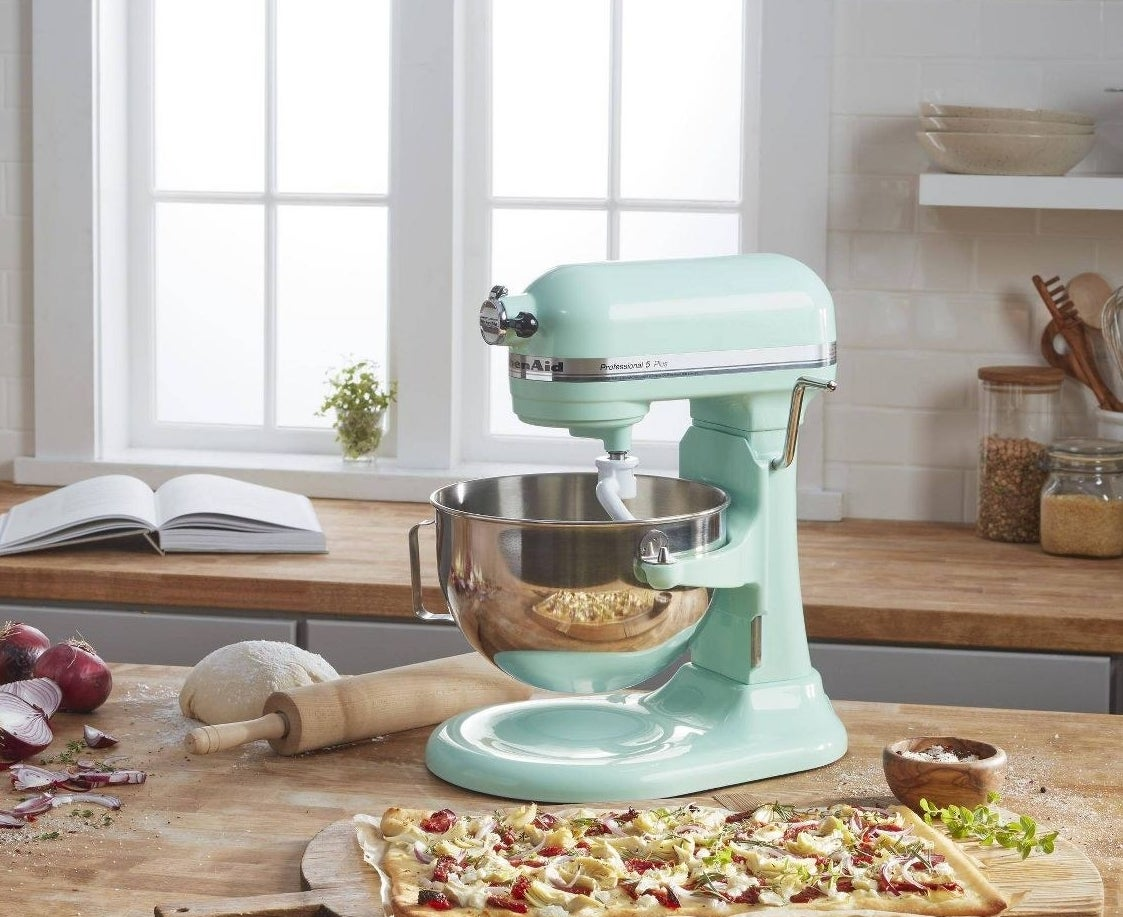 The standing mixer in turquoise in a kitchen preparing a flatbread