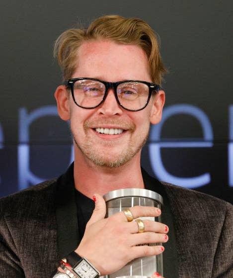Macaulay Culkin smiling, wearing glasses
