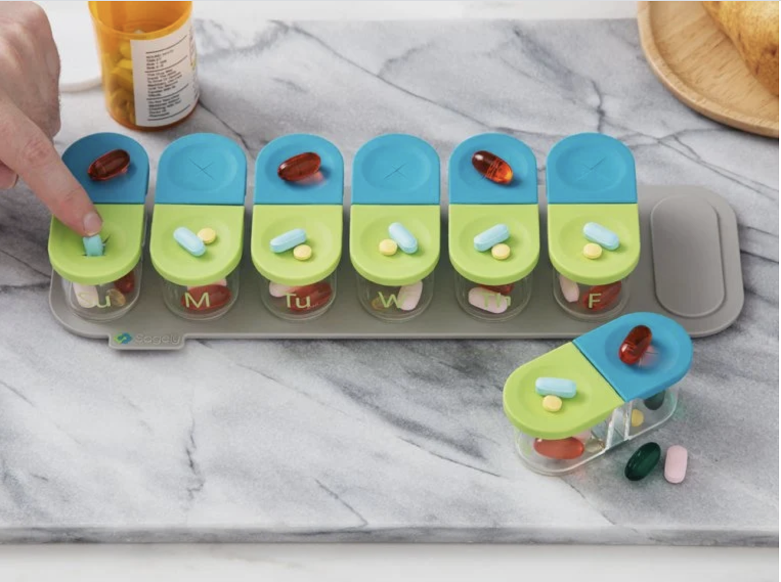 A set of seven transparent pill bottles with blue and green silicone lids dividing day and night propped on a gray magnetic holder