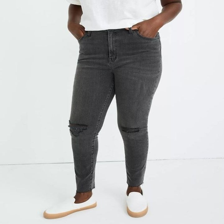 model in the grey high-waisted jeans with holes at the knees and frayed hems