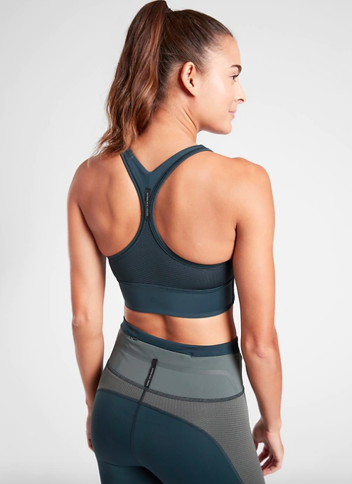 Model wears moss green high-neck bra with a criss-cross back