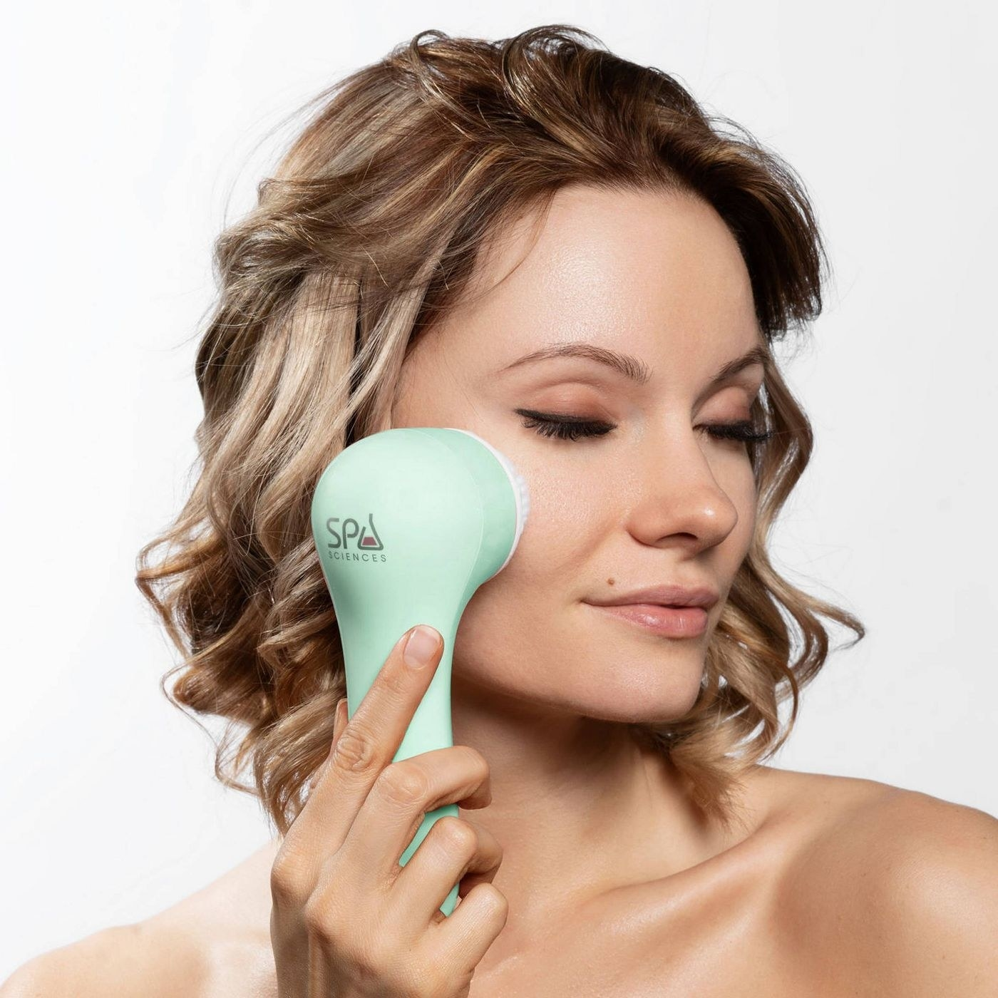The cleansing brush being used on a model's skin