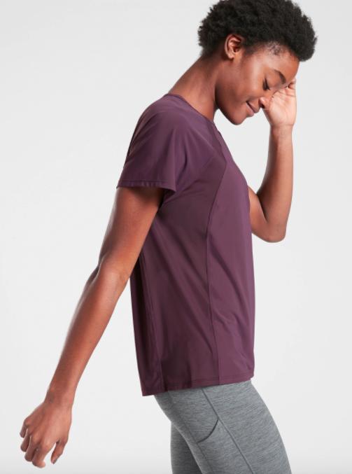 Model wears plum short-sleeve tee with panel detailing and light gray leggings