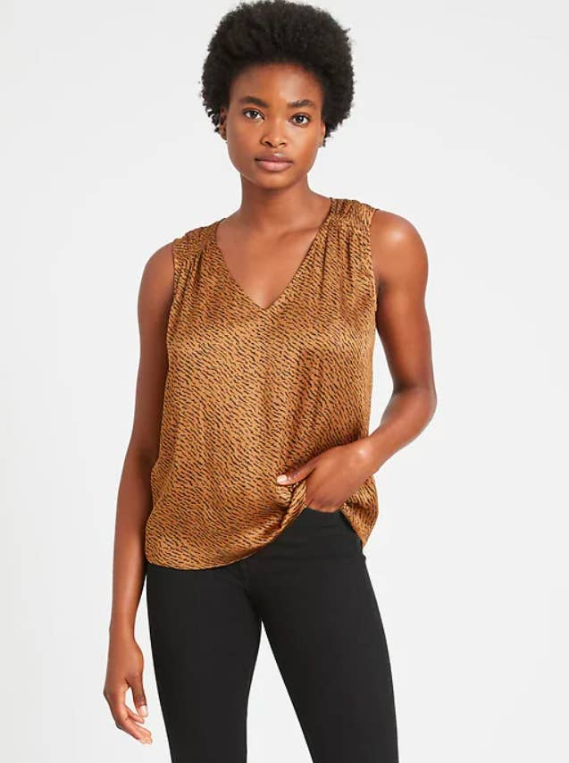 a model wearing the top in gold animal print