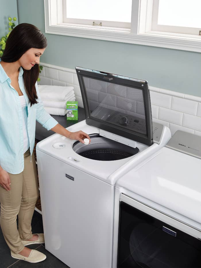 The cleaner, which is in tablet form, being dropped into a top-loading washer