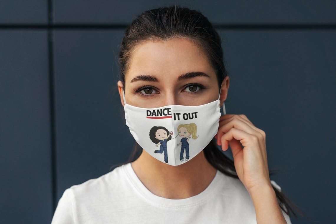 """White mask with illustrated versions of Cristina Yang and Meredith Grey from Grey's Anatomy and the words """"Dance It Out"""" on top"""