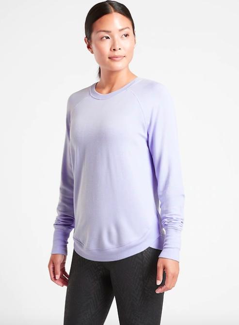 Model wears light purple long-sleeve sweatshirt with dark gray leggings