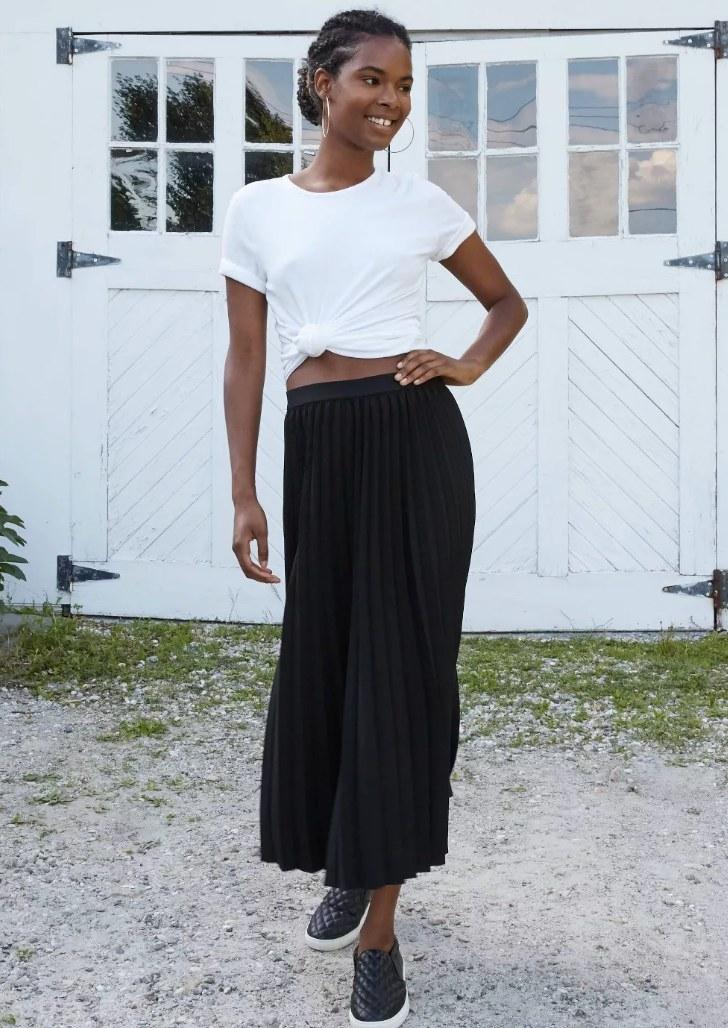 Model wearing long black skirt with white t-shirt