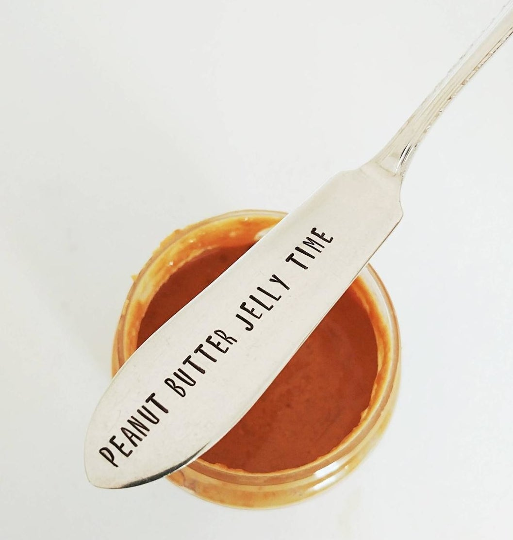 The spreader knife on top of a jar of peanut butter