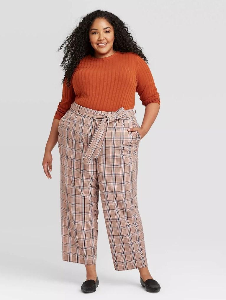 Model wearing light brown plaid pants with orange top