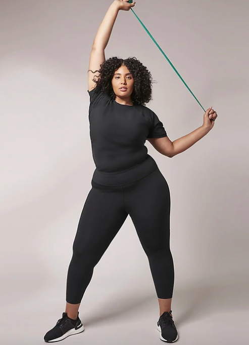 Model wears black t-shirt with black capri leggings while stretching an armband