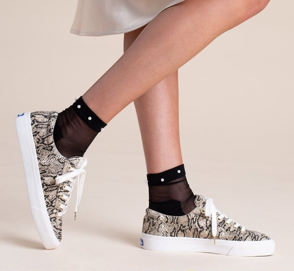 A person wearing the faux snakeskin Keds