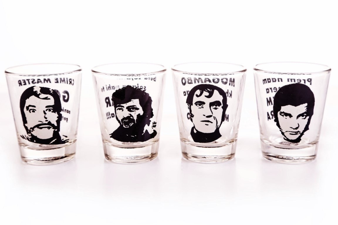4 shot glasses with faces of famous Bollywood villains on them.