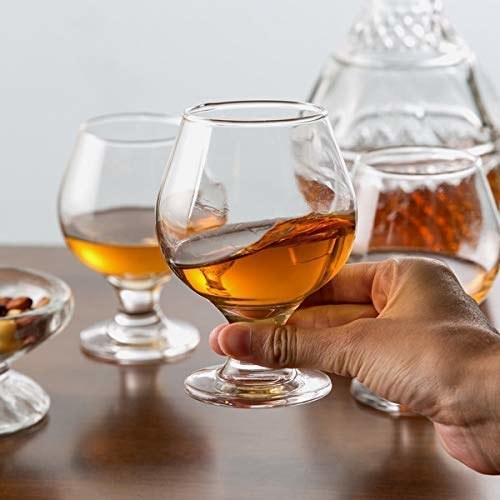 A person holding a brandy-filled glass.